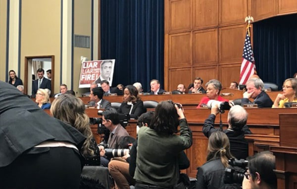 """Image: GOP staff put up a sign that reads """"Liar, liar, pants on fire"""" with a photo of Michael Cohen during his testimony on Capitol Hill on Feb. 27, 2019."""