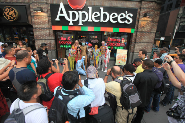 Nudists pose in front of an Applebee's restaurant near New York's Times Square as they participate in a public body painting event by artist Andy Golu...