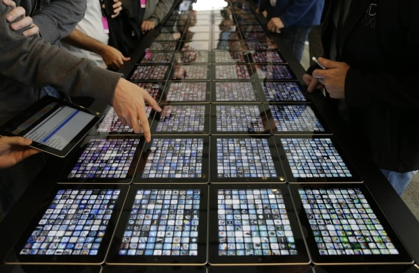 Developers look over new apps being displayed on iPads at the Apple Worldwide Developers Conference Monday, June 10, 2013 in San Francisco. (AP Photo/...