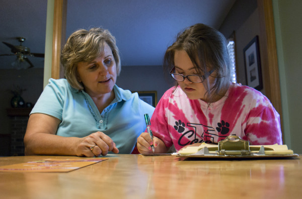 Jawanda Mast helps her daughter Rachel, 14, write thank you notes at their home in Olathe, KS, on  Aug. 6, 2013. Rachel has Downs Syndrome.