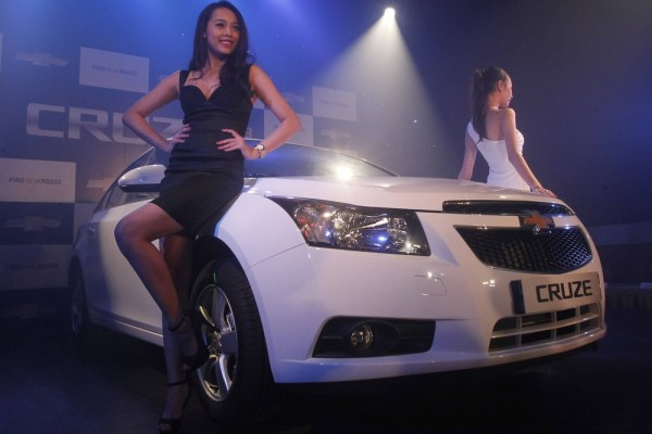 Models pose next to the new Chevrolet Cruze car of the 2013 series, during its launching ceremony in Hanoi June 19, 2013.                  According to General Motors...