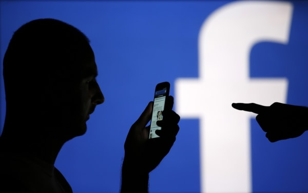 A man is silhouetted against a video screen with an Facebook logo as he poses with an Samsung S4 smartphone in this photo illustration taken in the ce...