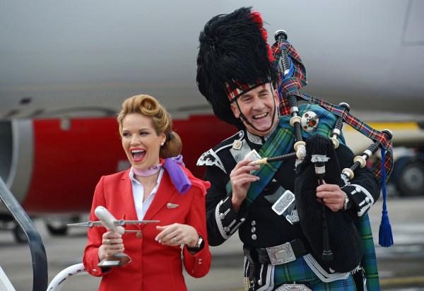 EDINBURGH, SCOTLAND - APRIL 08:  An air hostess reacts with a piper as Sir Richard Branson arrives in Edinburgh Airport wearing a Harris Tweed Kilt on...