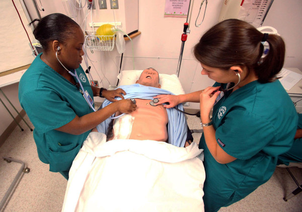 Nursing students Charlyndra Lucious, left, and Tiffany Pendley check the symptoms on a nursing dummy during a senior level associate degree nursing cl...