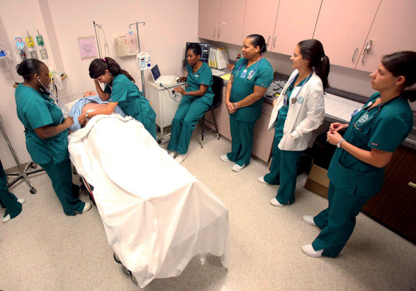 Nursing students check the symptoms on a nursing dummy during a senior level associate degree nursing class at Shelton State Community College in Tusc...