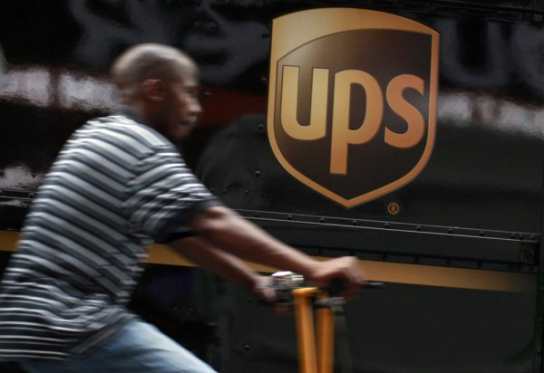 A bicycle delivery man rides past a United Parcel Service (UPS) truck in New York's Times Square in this July 23, 2012 file photo. United Parcel Servi...