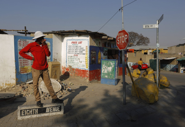 A man stands on the street sign for Eighth Avenue as he waits for a taxi in Alexandra Township, Johannesburg, South Africa, 01 October 2013.