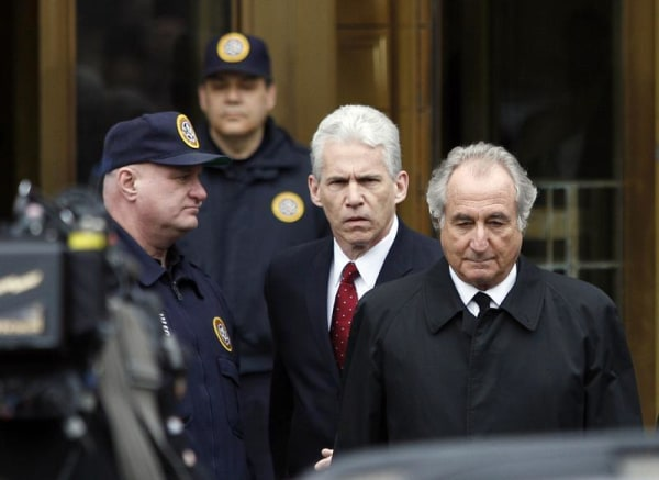 """Bernard Madoff, right, exits the Manhattan federal courthouse in New York in this March 10, 2009, file photo. Madoff says through his efforts, victims could be repaid all their original principal. He also claims he has information that """"would clearly demonstrate the vital role the major banks … played in the carrying out [of] my fraud."""""""