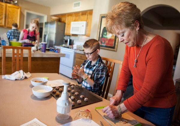 Leslie Davis helps her grandchildren bake holiday cookies on Saturday at her home in Mesa, Ariz.