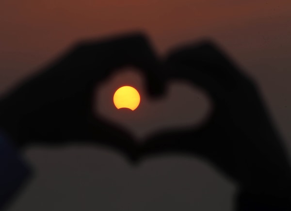 A Kuwaiti man makes the outline of a heart with his fingers to encompass a partially solar eclipse at Souq Sharq Marina in Kuwait City on November 3, 2013.