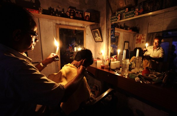 An Indian barber holding a candle,  has a haircut for a customer at his shop in Kolkata, India, Tuesday, July 31, 2012. India's energy crisis cascaded...