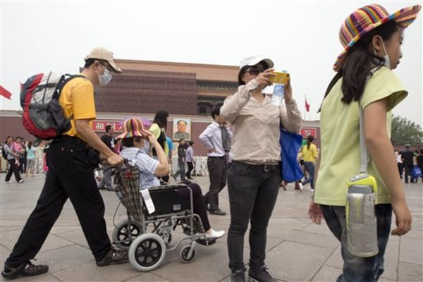 In this Tuesday, May 7, 2013 photo, visitors to Tiananmen Gate wear masks during a day of heavy pollution in Beijing. Air pollution significantly shor...