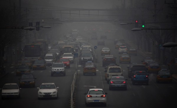 Cars drive along a street on a hazy day in Beijing January 29, 2013. Beijing temporarily shut down 103 heavily polluting factories and took 30 percent...