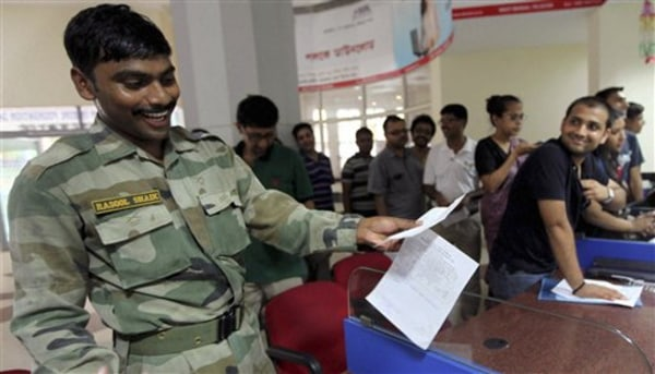 An Indian army soldier reacts as he prepares to send a telegram on the last day of the 163-year-old service at a telegraph office in Kolkata, India, S...