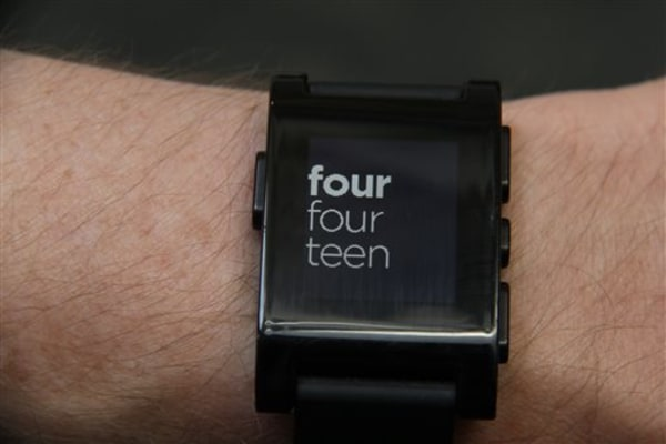 This photo taken July 16, 2013, shows the Pebble smart watch with customizable faces, this one showing the time written out in New York The watch func...