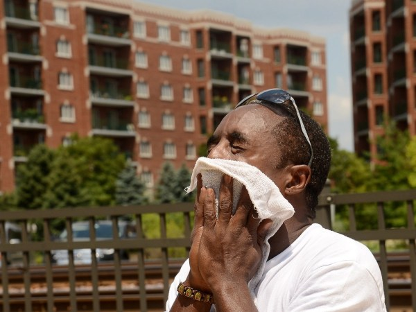 Jermaine Lumpkin, of D&J Amusements, towels himself off while setting up for Des Plaines Summer Fling in the heat Thursday, July 18, 2013. (AP Photo/D...