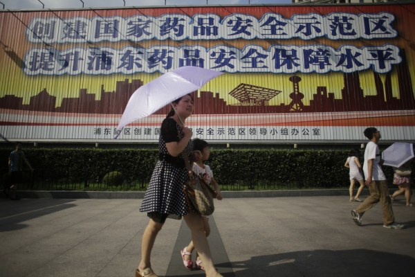 Tourists walk in front of a public service advertisement of drug safety in Shanghai, China, Monday, July 22, 2013.