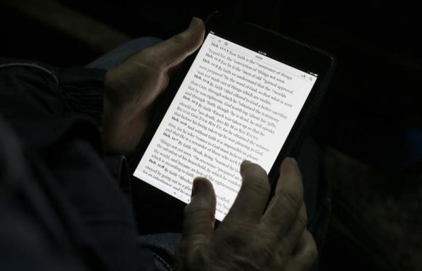 "A man reads the bible from an iPad mini at the ""Christ is the Answer International Ministries"" group's camp near Florence February 2, 2013. REUTERS/Ma..."