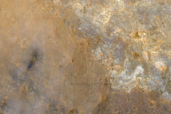 NASA's Mars rover Curiosity appears as a bluish dot near the lower right corner of this enhanced-color photo