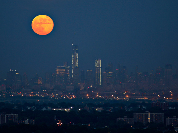 "A full moon also referred to as a ""super moon"" rises in the sky behind New York's Lower Manhattan and One World Trade Center as seen from the Eagle Ro..."