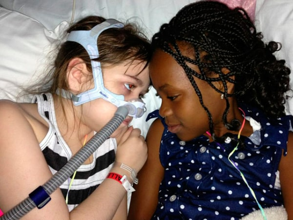 Sarah Murnaghan, left, lies in her hospital bed next to adopted sister Ella on the 100th day of her stay in Children's Hospital of Philadelphia.