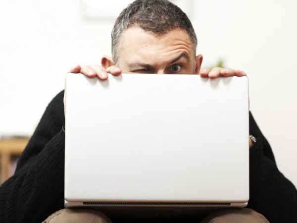 Man making faces from behind laptop; stock photography; computer; suspicious; raised eyebrow