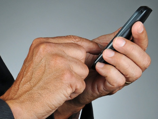 Closeup of a businessman dialing his cell phone. Horizontal format over a light to dark gray background. Man is unrecognizable.