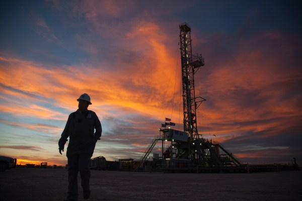 A worker walks from the 161-foot-tall rig to retrieve a tool from a nearby shed, Sunday, March 3, 2013, in West Texas.                                        When this picture was made o...