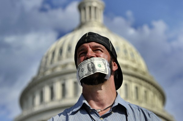A protester covers his mouth with a dollar bill