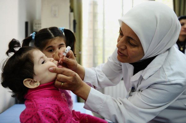 A health worker administers polio vaccine to a child as part of a UNICEF-supported vaccination campaign at the Abou ...