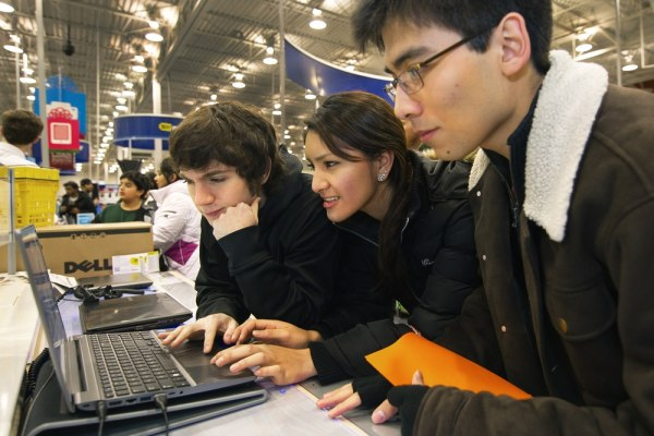 """Black Friday shoppers check out a Samsung I-Core 7 laptop on sale at the Fair Lakes Best Buy store in Fairfax, Va., in this Nov. 25, 2011, file photo. Retailers are fighting """"showrooming,"""" in which shoppers check out items in stores but then buy elsewhere online. Analysts like Best Buy's store-within-a-store concept, which lets customers interact with products and ask questions of dedicated salespeople."""
