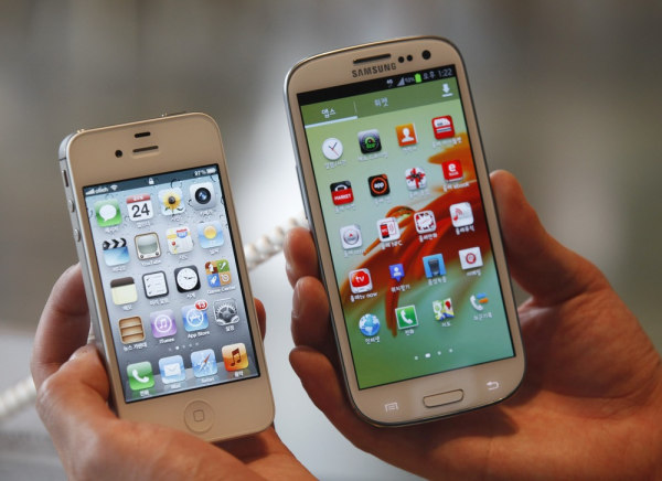 An employee poses as he holds Apple's iPhone 4s (left) and Samsung's Galaxy S III at a store in Seoul in this Aug. 24, 2012, file photo.