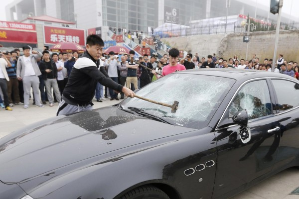 Talk about tuhao! This picture taken on May 14, 2013 shows men using sledgehammers on a Maserati car outside the Qingdao International Convention Cent...