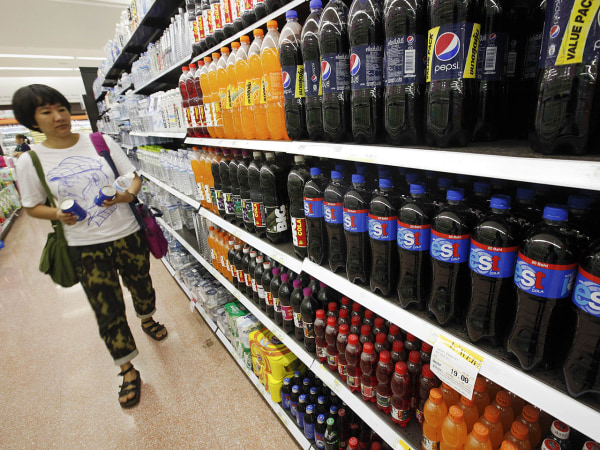 A customer walks past a shelf of soft drinks in Bangkok. A new study links sugar-sweetened sodas with endometrial cancer.
