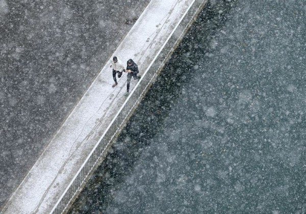 Two joggers run along the embankment of Aare river during the first snowfall in Bern November 21, 2013. REUTERS/Ruben Sprich