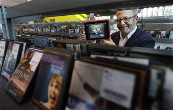 In this Sept. 11, 2013 photo, Kirk Blankenship, Electronic Resources Librarian for Seattle Public Libraries, poses for a photo in the DVD shelving are...