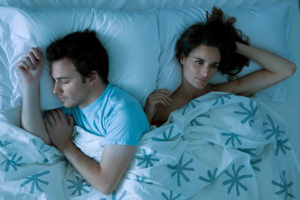 Couple lying together in bed, woman restlessly awake looking away bed night couple sex sleep
