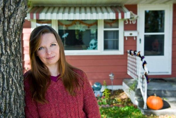 Anita Neisius stands in front of her home in Jamestown, N.D.