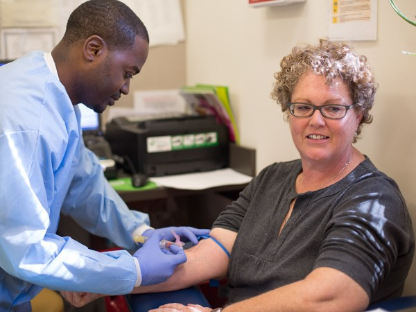 Abdul Muhammad, a group lead trainer for Quest Diagnostics, draws blood from Melanie Mitsui at Mary's Center