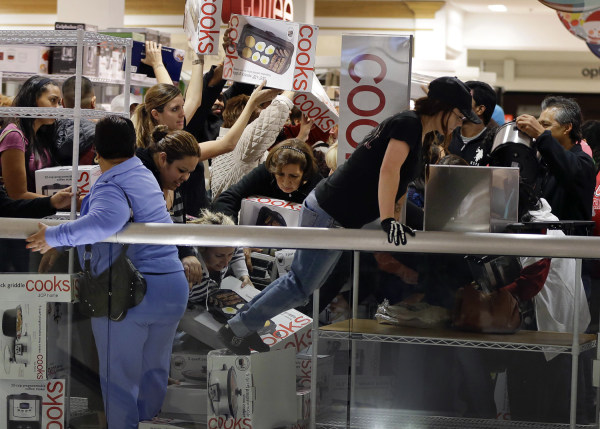 Shoppers rush to grab electric griddles and slow cookers on sale for $8 shortly after the doors opened at a J.C. Penney story, Friday, Nov. 23, 2012, ...