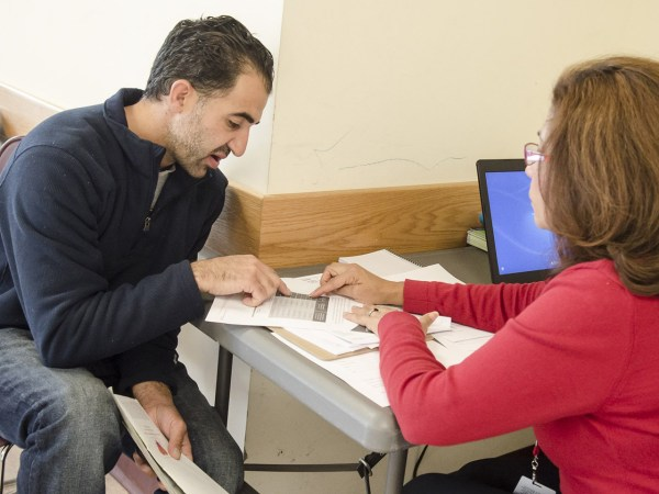 Martha Lopez of Community Clinics, Inc, right, explains to Amine Ashkar of Burtonville, Md., benefits that he and his family would receive under the n...
