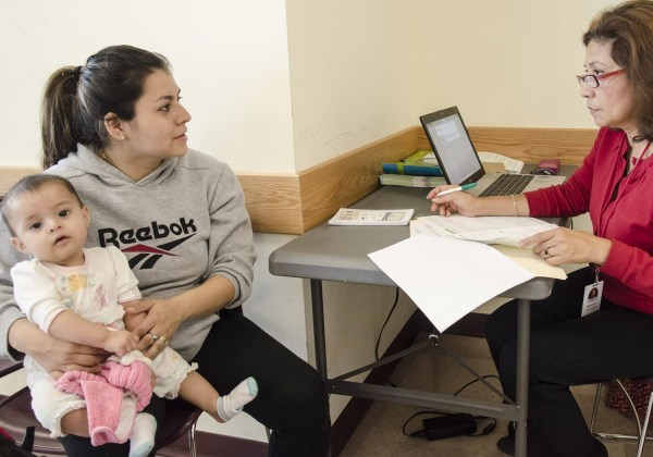 Martha Lopez of Community Clinics, Inc (R) helps Griselda Fernandez Mata(L) of Adelphi, Md fill out a paper application to receive benefits under the new Obamacare plan at the WIC(Women, Infants and Children Service) center at the Wheaton Mall in Wheaton, Md