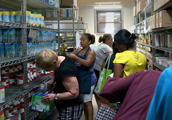 Volunteers help food bank clients in the pantry of the West Side Campaign Against Hunger food bank in New York City. The food bank assists thousands of qualifying New York residents in providing a monthly allotment of food.