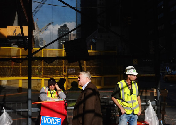 Pedestrians and workers stand by an entrance gate to the World Trade Center site in November 2011 in New York City.