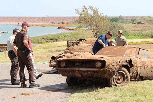 Police officers look at a car containing skeletal remains found at the bottom of Foss Lake in Custer County.