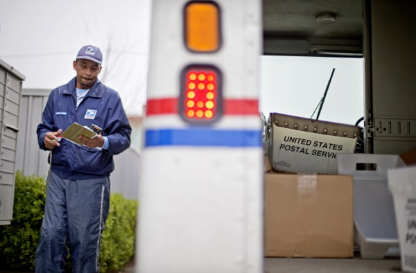 A empty mail bin sits in the back of a truck as U.S. Postal Service letter carrier of 19 years, Michael McDonald, delivers mail, Thursday, Feb. 7, 201...