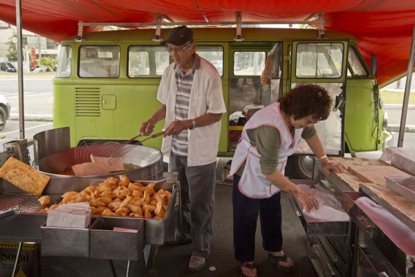 In this Sept. 3, 2013 photo, Jorge Hanashiro and his wife Ana, prepare deep fried meat and vegetable pastry pies at an open-air market, with their lig...