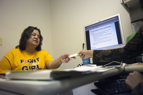 Wanda Perry, 48, is counseled by a marketplace guide about her options regarding the Health Insurance Marketplace. The new exchanges, a centerpiece of health reform, go live Tuesday.