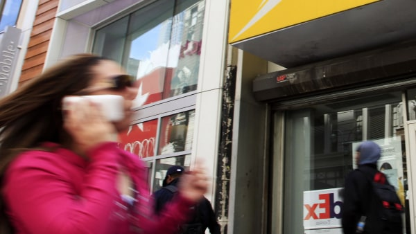 A woman using a cell phone walks past T-Mobile and Sprint stores, Tuesday, April 27, 2010, in New York. Sprint Nextel Corp. on Wednesday, April 28, sa...