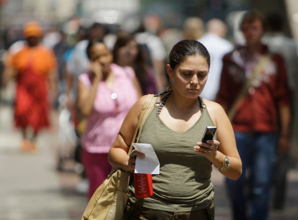 Yvette M. uses her cell phone to text message friends while walking in downtown street, Tuesday, July, 29, 2008, in Chicago. In an alert issued this w...